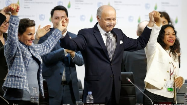French Foreign Affairs Minister Laurent Fabius, centre, who chaired the Paris climate talks, and Christiana Figueres, left, executive secretary of the UN Framework Convention on Climate Change, celebrate at the close of the summit on Saturday. With a global deal in hand, now begins the tough work of adhering to it, scientists say.