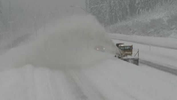 A snowplow pushes snow off the summit of the Coquihalla Highway.
