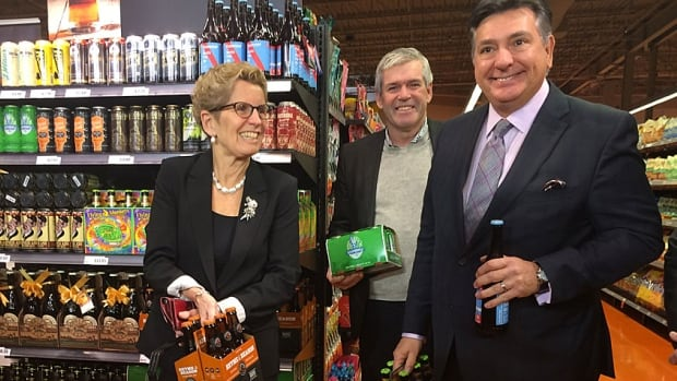 Ontario Premier Kathleen Wynne, left, smiles as she buys beer at a Toronto Loblaws grocery store on Tuesday morning alongside MPP Arthur Potts, centre, and Finance Minister Charles Sousa, right.