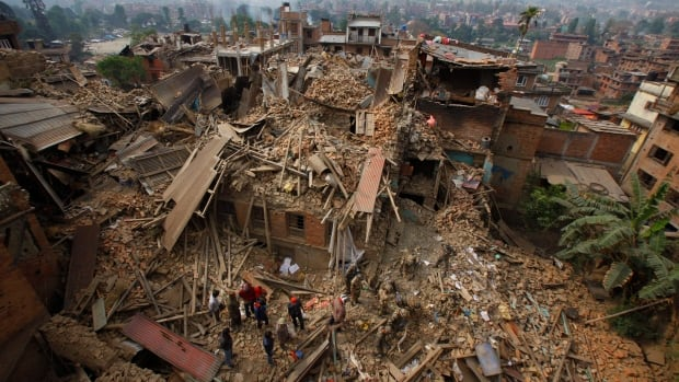 Rescue workers remove debris as they search for victims of earthquake in Bhaktapur near Kathmandu, Nepal, Sunday, April 26, 2015. A strong earthquake shook Nepal's capital and the densely populated Kathmandu Valley before noon, causing extensive damage with toppled walls and collapsed buildings. (AP Photo/Niranjan Shrestha, File)