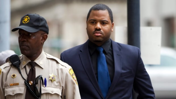 Officer William Porter, right, one of six Baltimore city police officers charged in connection to the death of Freddie Gray, arrives at a courthouse on Wednesday.