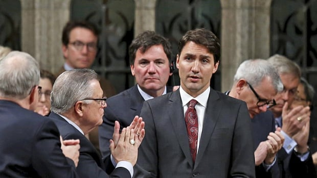 Liberal Leader Justin Trudeau receives a standing ovation from his caucus in March after voting against the Harper government's plan to expand airstrikes against ISIS. He still hasn't spelled out what exactly he will do instead.