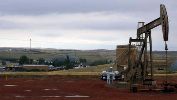 In this Sept. 5, 2015, photo, a pump jack pumps oil on a hill above Alexander, N.D., and the town's school.  The U.S., seemingly awash in crude oil after an energy boom sent thousands of workers to the plains of Texas and North Dakota, will begin exporting oil for the first time since the 1973 oil embargo.