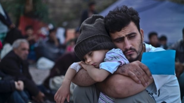 A Syrian man and his child wait in a refugee camp in Greece last fall. More than 988 refugees have come to Hamilton, and public health officials are rushing to make sure they have proper vaccinations.