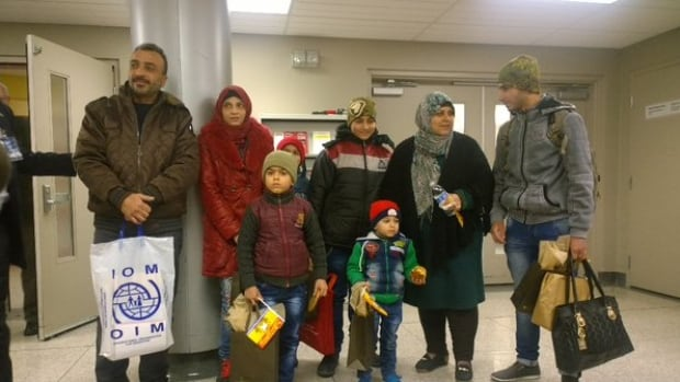 The first Syrian refugee family arrives in Fredericton on Dec. 19 to an arrivals-area assembly of smiles, signs and balloons.