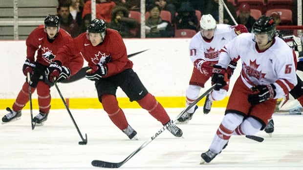 Team Canada's Travis Dermott (centre left) brings the puck up the ice during third period action in an exhibition game against the CIS all-stars in Toronto on Dec. ahead of the world junior championships.
