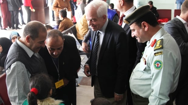 Canadian Minister of Immigration John McCallum, centre, talks on Sunday with a Syrian family soon to be flown to Canada. McCallum said the country's resettlement program for Syrian refugees could double by the end of 2016.