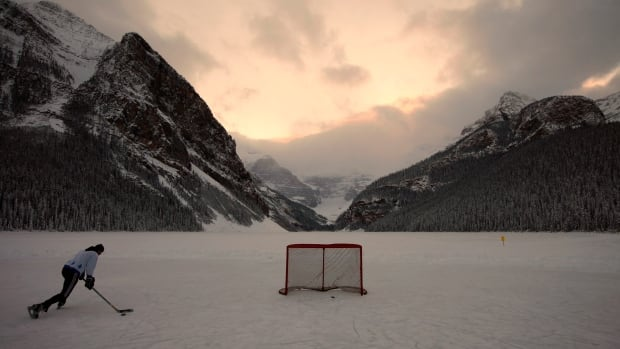 A hockey player skates on Lake Louise in the Canadian Rocky Mountains, Alta. in December 2010. Winters as Canada knew them may soon be a thing of the past as climate change progresses.