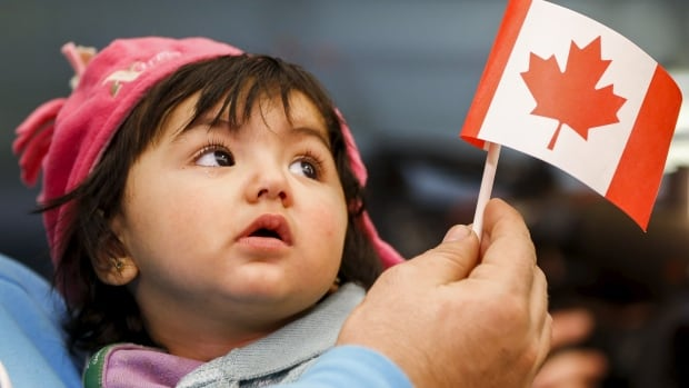 A young Syrian refugee looks up as her father holds her and a Canadian flag at the as they arrive in Toronto on Dec. 18. While many Canadians are privately sponsoring Syrian families, some are taking on refugees from other countries, instead.
