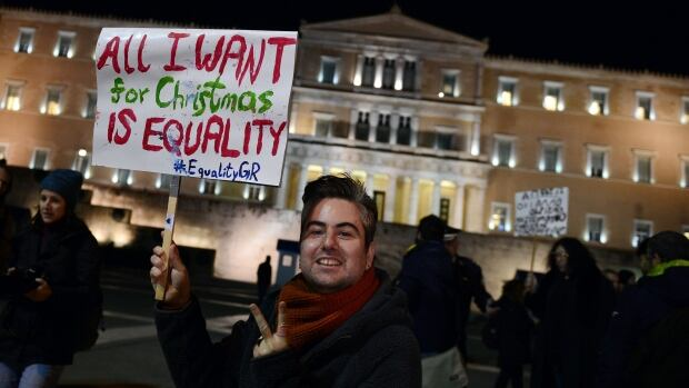 A man holds a placard during a demonstration outside the Greek parliament in Athens, where lawmakers voted early Wednesday to allow gay couples the right to have civil partnerships.