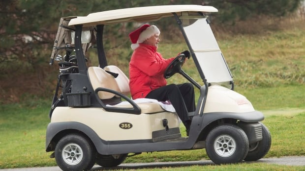 Gary Laughlin golfs in a Santa hat at Lionhead Golf & Country Club in Brampton, Ont., on Wednesday, December 23, 2015.