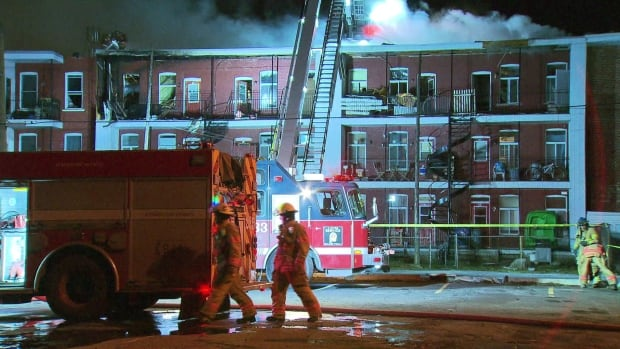 Firefighters work to contain the blaze, which started on the third floor of the three-story building.