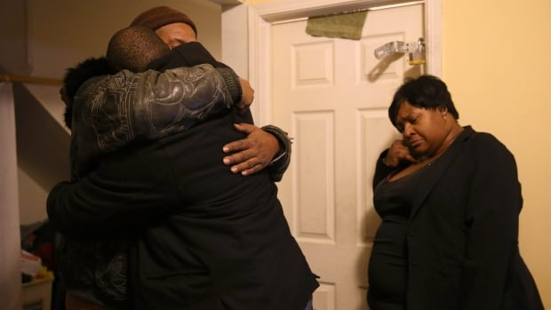 Melvin Jones, facing camera, hugs Robin Andrews, both brothers of Bettie Jones, 55, in Jones' living room after she was shot and killed by a Chicago police officer in Chicago on Saturday, Dec. 26, 2015.