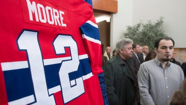 People wait in line to pay their respects during the public visitation of Montreal Canadiens hockey legend Dickie Moore on Sunday.