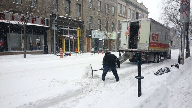 A man shovels the outside walkway outside of a business on Ste-Catherine Street in Montreal.