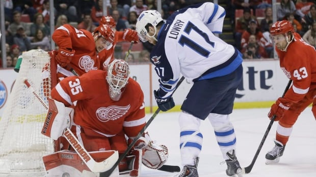 Detroit Red Wings goalie Jimmy Howard stops a shot by Winnipeg Jets left wing Adam Lowry (17) during the second period of an NHL hockey game, Saturday, Feb. 14, 2015 in Detroit.