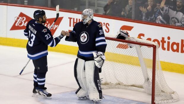 Winnipeg Jets' Dustin Byfuglien (33) and goalie Connor Hellebuyck (30) celebrate after the team defeated the Detroit Red Wings following third period NHL hockey action, in Winnipeg, on Tuesday.