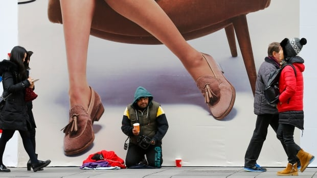 A beggar kneels in front of an advertising billboard in the centre of Vienna in November. If world economies weaken in 2016 it will become harder to narrow the gap between rich and poor.