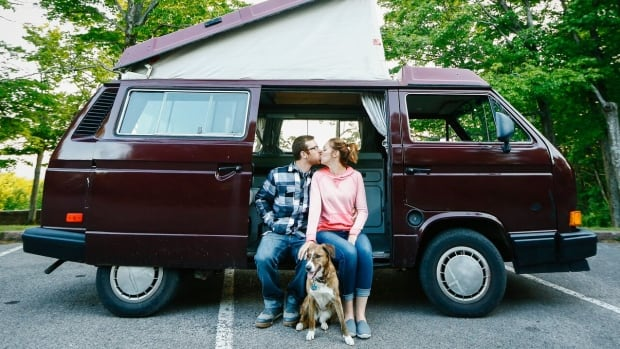 John Rathwell, Tracy Guenard and their dog, Rain, sit on the edge of their camper-van before the engine was stripped for extensive restoration ahead of their two-year roadtrip to promote mental health.