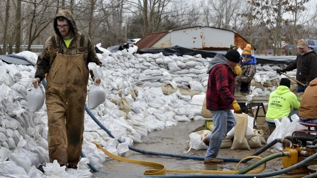Volunteers create a wall of sandbags to protect homes from flooding after several days of heavy rain in Arnold, Miss., on Wednesday.
