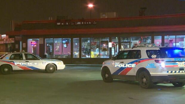 Police surround a Coffee Time connected to a gas station in the Jane St. and Wilson Ave. area Thursday night after a young man was slashed with a machete by an unknown assailant.