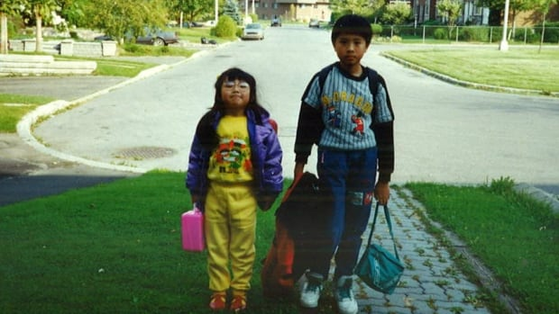 Elaine Chau, age 6, and her brother Edmond, outside their Montreal house in 1992, the year the family moved to Canada from Hong Kong.