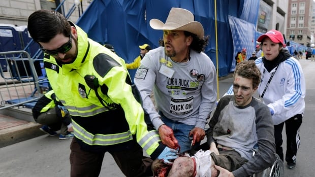 One of the injured is helped after two bomb blasts near the finish line of the 2013 Boston Marathon. A new feature-length documentary joins a growing list of projects in production involving the marathon.