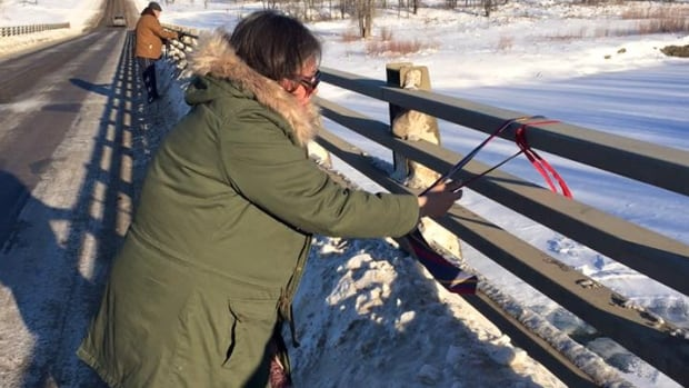 Colten Pratt's mother Lydia Daniels wraps a men's tie around a guard rail on Long Plain First Nation.