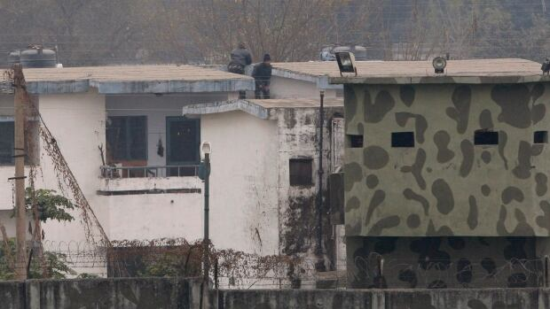 Indian soldiers are seen on a rooftop at an airbase in Pathankot, India, on Monday. After saying all the gunmen who attacked the Indian airbase near the Pakistan border were dead, Indian officials said at least two attackers remained.