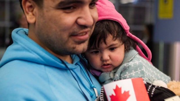 Syrian refugee Osama (left) holds his daughter as they as they arrive with other families at Toronto's Pearson Airport last month. Feel-good stories about refugee arrivals aren't helpful because they inspire complacency, Steven Zhou says.