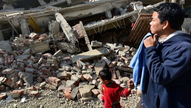 A man and his son pass a damaged house after a magnitude 6.7 earthquake struck Imphal, northeast India, on Monday.