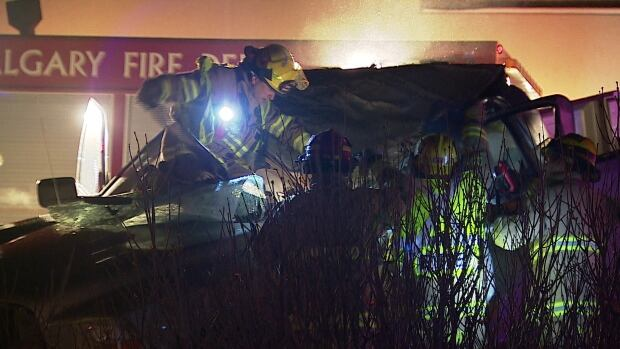 Fire crews work to extract a man from his pick up truck, which rolled over at Crowchild Trail and Bow Trail.