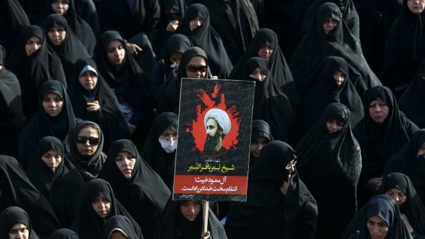 An Iranian woman holds up a poster showing Sheikh Nimr al-Nimr, a prominent Shia cleric who was executed by Saudi Arabia, during a protest in Tehran on Monday, Jan. 4, 2016.