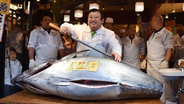 Sushi boss Kiyoshi Kimura poses with the 200 kg bluefin tuna he bought at the first fish auction of the year, at his main restaurant near Tokyo's Tsukiji fish market, on Tuesday.