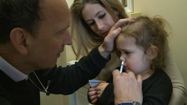 Westmount pediatrician Dr. John Yaremko gives a child-friendly nasal mist flu vaccine to a three-year-old patient.