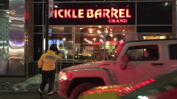 A police officer on the scene after a stabbing near the Pickle Barrel near Yonge and Dundas streets.