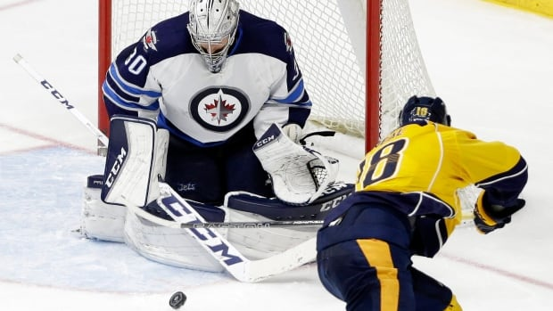 Winnipeg Jets goalie Connor Hellebuyck (30) blocks a shot by Nashville Predators left wing James Neal (18) in the third period of a game Tuesday, Jan. 5, 2016, in Nashville, Tenn.