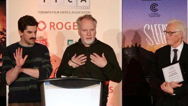 The Forbidden Room co-directors Evan Johnson, left, and Guy Maddin accepted the $100,000 best Canadian film award at the Toronto Film Critics Association Awards gala on Tuesday. Association president Brian Johnson looks on from the right.