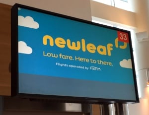NewLeaf Travel Company sign at Winnipeg airport