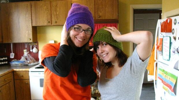 Sami Lester, left, and Alexandra Pesant-Tremblay model hats Lester made after learning how to knit during her stint in the Katimavik program. Lester started a petition urging Justin Trudeau's government to restore funding for the national youth service program.
