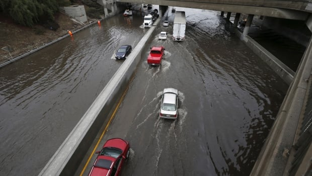Vehicles drive on the flooded 5 freeway after an El Nino-strengthened storm brought rain to Los Angeles, Wednesday.