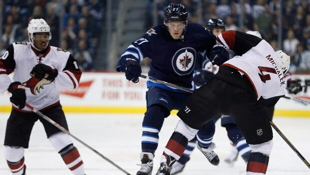Winnipeg Jets forward Nikolaj Ehlers (27) and Zbynek Michalek (4) of the Arizona Coyotes collide during the second period of a game Nov. 21 in Winnipeg. The NHL says Ehlers received a warning after that game about diving and embellishment.