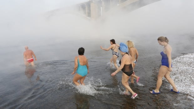 Mikhail Sashko, out in front, celebrates his 68th birthday by leading a group of fellow Cryophile swim club members into the Yenisei River on Nov. 21, 2015, when it was -27 C.