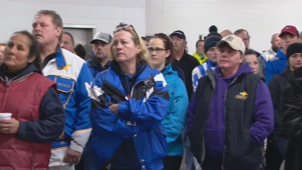 Members of the horse racing community watch a video tribute to 43 horses that were killed in a barn fire earlier this week.