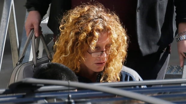 Tonya Couch is escorted to a waiting vehicle after her arrival to the Dallas-Fort Worth International Airport in Grapevine, Texas, on Thursday.