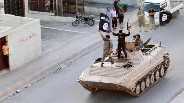 ISIS fighters take part in a military parade along the streets of northern Raqqa province June 30, 2014. Activists say a militant in the ISIS-held city killed his own mother in front of a large crowd recently because she was deemed a non-believer.