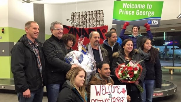 Pastor Mark Wessner, left, and Prince George Mayor Lyn Hall, next left, pose with Syrian newcomers and well-wishers at the Prince George airport on Jan.8, 2015.
