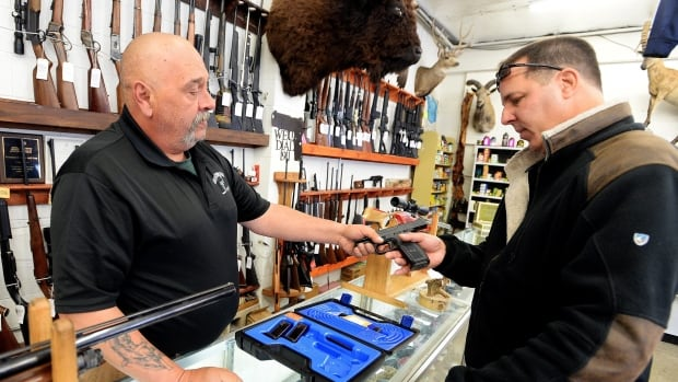 Bill Karnok, left, of Grandpa's Pawn Shop in Longmont, Colo., shows a gun to a customer on Tuesday, Jan. 5, 2016 - the day President Barack Obama unveiled his plans to tighten control and enforcement of firearms in the U.S. (Cliff Grassmick/Daily Camera via AP)