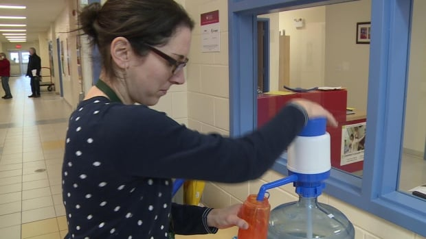 A staff member at École Saint-Augustin gets a drink of bottled water.