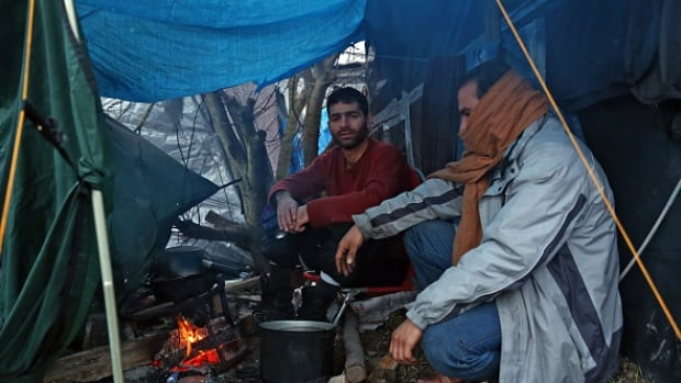 Iranian migrants cook food in a shelter in the camp known as 'The Jungle' on January 5, 2016 in Calais, France.